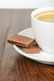 Half cup of coffee with chocolate on table Stock Photography