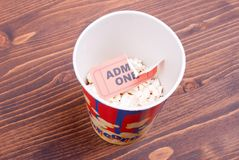 Half cup of popcorn, used ticket on the table top view Royalty Free Stock Photos