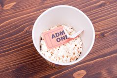 Half cup of popcorn, used ticket on the table top view Stock Photography