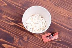 Half cup of popcorn, used ticket on the table top view Stock Photo