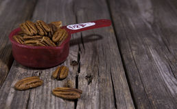 A half cup of raw natural almonds. A red half cup of raw almonds on a rustic wooden background Royalty Free Stock Photos