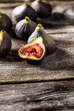 Half cut fig with other ripe figs on wooden background Stock Images