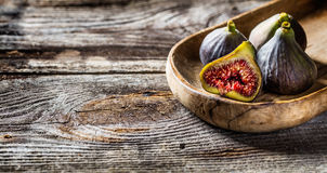 Half cut fig with other ripe figs in wooden tray Stock Photography