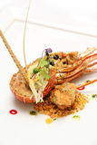Half cut lobster with golden flakes. Served on white plate Royalty Free Stock Image