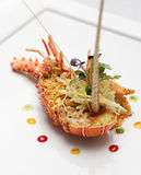 Half cut lobster with golden flakes. Served on white plate Stock Image