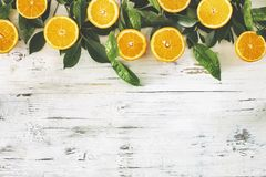 Half cut orange fruit and leaf on the vintage wooden background. Half cut orange fruit and leaf  on the vintage wooden background Royalty Free Stock Photography