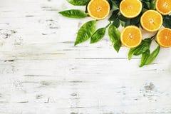 Half cut orange fruit and leaf on the vintage wooden background. Half cut orange fruit and leaf  on the vintage wooden background Stock Photos