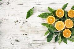 Half cut orange fruit and leaf on the vintage wooden background. Half cut orange fruit and leaf  on the vintage wooden background Royalty Free Stock Images