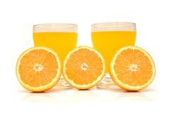 Half-cut oranges and fresh ora. Nge juice Royalty Free Stock Photography
