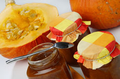 Half of cut pumpkin and three marmalade jars. On table Royalty Free Stock Images