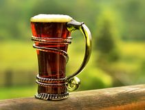 Half dark beer in a vintage artistic green glass royalty free stock image