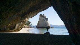Young woman standing below Cathedral Cove in Coromandel, New Zealand stock images