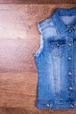 Half of denim tank top, space for text. Free space near denim cape Royalty Free Stock Photo