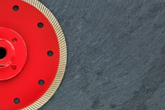 Half of the diamond cutting wheel is red with a threaded nut on a background of gray granite royalty free stock images