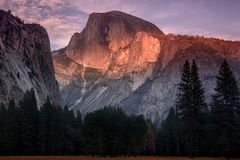 The Half dome on fire at sunset. Redening sunset rays over yosemite half dome Stock Photos