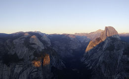 Half Dome from Glacier Point. High-resolution panorama of Yosemite valley shrouded by the evening gloom with Half Dome lit by the setting sun Stock Photos