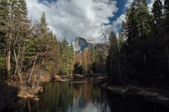 Half Dome with Mid Day Clouds and Reflection Stock Images