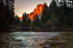 Half Dome Sunset. Golden Sunlight On Half Dome With Merced River and Stoneman Bridge In Foreground Stock Photo