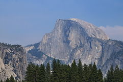 Half Dome in Yosemite, California. Half Dome monolith. Trees at foreground. Blue sky at background Stock Photo