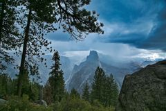 Half dome Yosemite National Park. High view of half dome mountain with ominous dark thunderstorm clouds forming and green trees in foreground stock photos
