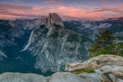 Half Dome at Yosemite National Park. Half Dome at Yosemite at Sunset.  View from a ledge with a log in front Royalty Free Stock Images