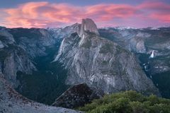 Half Dome and Yosemite Valley in Yosemite National Park during colorful sunset with trees and rocks. California, USA. Sunny day in the most popular viewpoint in stock photo