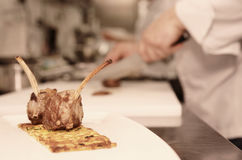 Half done meat dish with chef  in background Stock Image