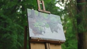 The drawing stands on an easel in the middle of the meadow in a green park. Half drawn landscape of a summer park. Figure how it is worth on. The drawing stands stock footage