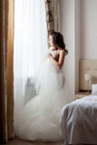 Half-dressed bride looks thoughtfully at window Stock Images