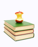 Half-eaten apple on a stack of books Stock Images