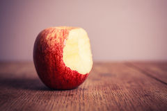 Half eaten apple on wooden table Royalty Free Stock Photos