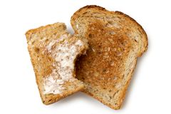 Half eaten buttered slice of whole wheat toast and whole dry sli Stock Photos
