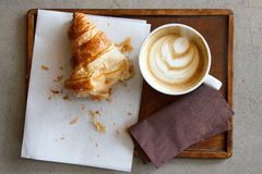 Half eaten croissant with cappuccino on wood tray from above. Royalty Free Stock Image
