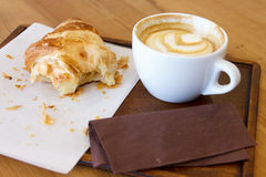 Half eaten croissant with cappuccino on wood tray and table. Royalty Free Stock Image