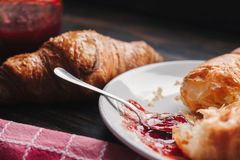 Half eaten croissant on white plate with spoon of jam, with some jam spilled on a plate. In the background on the table is another croissant, jar of jam and stock photo