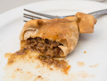 Half eaten empanada. On white plate with sauce, meat and spices spilling onto the plate and a fork behind Stock Images