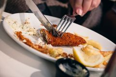 Half eaten fish and chips dish being cut using cutlery by a woma Stock Photo