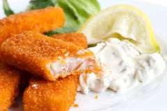 Half eaten fish fingers with lemon and tartar sauce Royalty Free Stock Images