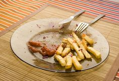 Half eaten french fries. On the plate Stock Photos