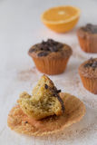 Half eaten muffin. Very moist and tender. Half eaten orange and dark chocolate muffin with some more muffins in the background royalty free stock photos