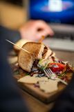 Half Eaten Sandwich On Wooden Plate Royalty Free Stock Photography