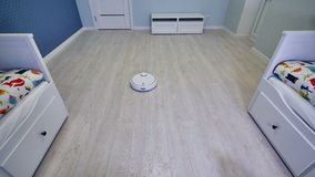 A half-empty childrens room cleaned fast by a robotic vacuum cleaner. stock footage