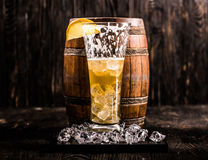 Half empty glass of beer and ice with barrel on the background Royalty Free Stock Photography