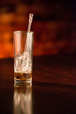 Half empty glass of cola with chewed straw and copyspace Stock Image