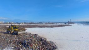 A large half-empty landfill with a working compactor. Enviromet pollution concept. A half-empty landfill with a working compactor and factory buildings in the stock footage