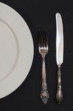 Half empty white plates, vintage knife and fork on  table. Half empty white plates, vintage knife and fork on black table, view from above Royalty Free Stock Images