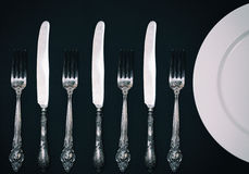 Half empty white plates, vintage knife and fork on  table. Half empty white plates, vintage knife and fork on black table, view from above Royalty Free Stock Photo