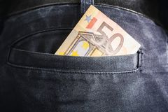 Half Of A 50 Euro Bill Showing Out Of The Back Pocket Of A Black Jeans Trouser - Rich Man Concept stock images