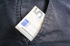 Half Of A 5 Euro Bill Showing Out Of The Pocket Of A Black Jeans Trouser - Poor Man Concept royalty free stock photography