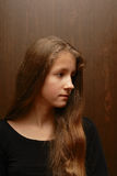 Half face. Portrait of teenage girl with long hair against dark brown background Stock Photo